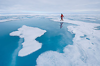 Atop some floes ice melts into turquoise pools of water and a scientist is sampling the water to determine what life might exist.
