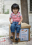 In Amman, Jordan, 4-year old Baha, a refugee from Damascus, Syria, sits on a box of household supplies his family received from International Orthodox Christian Charities, a member of the ACT Alliance. <br />  <br /> Parental consent obtained.