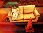 Doll with umbrella sitting on couch in rain by Hazard Cone, with flame effect at edge. 1950's plastic life-sized toddler girl doll.