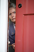 Older woman looking through door using a safety chain. MR