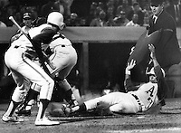 Oakland A's Reggie Jackson slides safe at home. Rick Monday on left, Jackson scored on sac fly by Danny Cater. (1969 photo by Ron Riesterer_