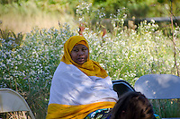 Young woman watching music at Somali Bantu harvest festival, Maine
