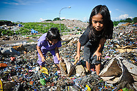 Annie, 11, and Erni, 10, searching for plastic and metal to recycle amongst newly dumped waste at the 'Trash mountain', Makassar, Sulawesi, Indonesia.