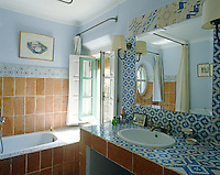 Patterned blue and white glazed tiles line the walls and washstand in this Mediterranean-style bathroom