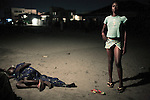 KINSHASA, DEMOCRATIC REPUBLIC OF CONGO - APRIL 29: Betty Nginamawu (r), age 14, solicit clients as her friend has collapsed of an overdose of Valium and homemade Whiskey on April 29, 2006 in Matonge district in central Kinshasa, Congo, DRC. Betty is homeless and works as a prostitute together with friends. Betty has been on the streets for a few years, and has been rejected by her family. From time to time, she lives in a homeless shelter for but doesn't like the rules there. She was recently rejected from the shelter as she brought in Valium to give the other girls. She usually smokes cigarettes, marijuana and drinks whiskey. She charges the clients as little as US$ 1. About 15,000 children are estimated to live on the streets of Kinshasa. Congo, DRC is in ruins after forty years of mismanagement by the corrupt dictator and former president Mobuto Sese Seko. He fled the country in 1997 and a civil war started. The country is planning to hold general elections by July 2006, the first democratic elections in forty years.(Photo by Per-Anders Pettersson)