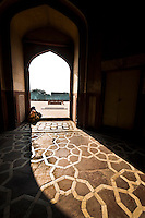 Two women sitting on the arched doorway of Humayun's Tomb.  Humayun was one of the great Mughal emperors who reigned during the 16th century. (Photo by Matt Considine - Images of Asia Collection)