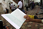 A Palestinian muslim reads the holy Qur'an at mosque, during the holy month of Ramadan in West Bank City of Nablus, on June 30, 2014. Muslims around the world refrain from eating, drinking and sexual intercourse from dawn till dusk during Ramadan, the holiest month in the Islamic calendar. Photo by Nedal Eshtayah