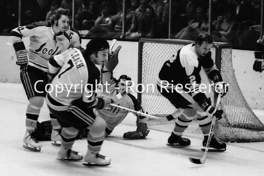 California Golden Seals action, Dick Redmond, Reggie Leach, and goalie Gilles Meloche. defend #12 Wayne Cashman. (photo/Ron Riesterer)