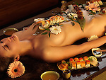 Beautiful nude asian woman lying naked on the table with sushi rolls and flowers on her naked body. Japanese Nyotaimori.