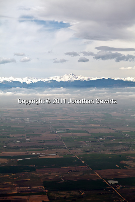 Aerial view of the Rocky Mountains and their foothills near Denver, Colorado, and of farmland in the adjacent plains.