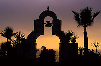 church doorway and bell tower with palm trees silhouetted agaist the sunset in Baja California