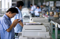 Workers checking print quality from renovated second-hand copiers in Ecostar factory, Nanjing, Jiangsu Province, China