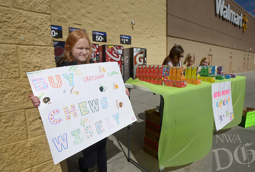 NWA Democrat-Gazette/BEN GOFF @NWABENGOFF<br /> Emily Starkey (from left), 8, Emma Griggs, 9, Caroline Barnett, 9, and Olivia Tingley, 8, with Girl Scout Brownie Troop 5343 sell cookies Saturday, March 12, 2017, outside the Wal-Mart on Elm Springs Road in Springdale. The troop plans to donate $200 from the sale to the Springdale Animal Shelter and was also accepting donations to give cookies to the Springdale Police Department.