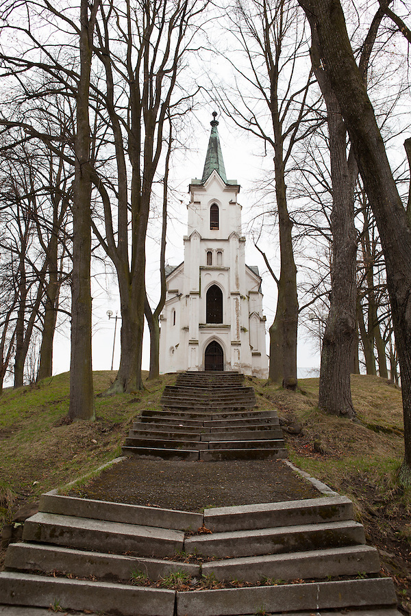Several steps lead to a white church on a hill in Pelhřímov, a popular town to visit in southern Bohemia with a lovely town square, Czech Republic, Europe