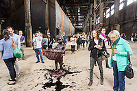 """A Subtlety"" or ""The Marvelous Sugar Baby"" by the artist Kara Walker is displayed in the former Domino Sugar Factory in Williamsburg, Brooklyn in New York seen on Saturday, May 24, 2014. A giant sphinx-like figure, 75 feet long made of 160,000 pounds of sugar on a polystyrene core is the centerpiece of the exhibit which is located in the sugar factory that has been closed for a decade and is scheduled to be torn down to make way for development. Walker also created a series of ""Candy Boys"" sugar sculptures which dot the rest of the warehouse. The sugar comprising the ""Candy Boys"" is melting out in the non-climate controlled warehouse leaving molasses on the already sugar coated floor. The exhibit is part of Creative Time and will run until July 6. (© Richard B. Levine)"