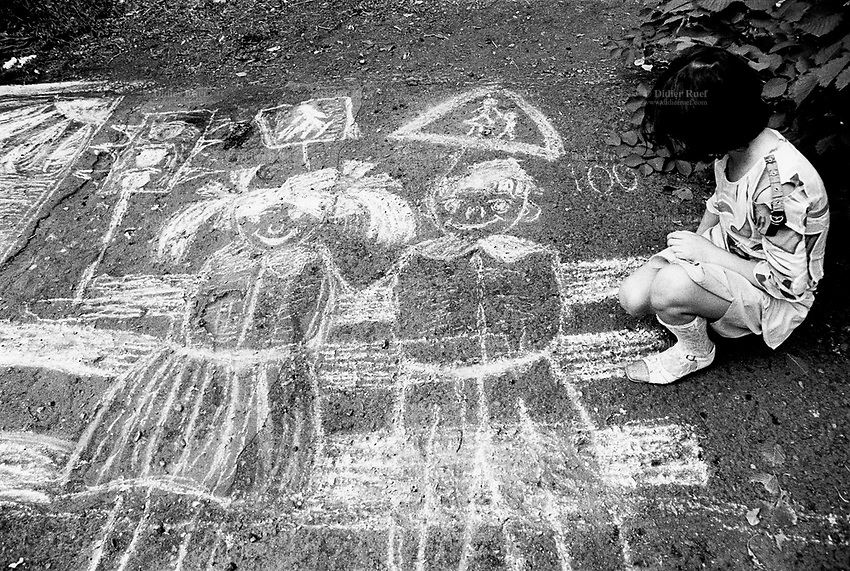 "Kazakhstan. Semipalatinsk. The first of june is ""Children Defense Day"". A girl with a white chalk sketches a couple of happy children and traffic lights on the ground of the park. Semipalatinsk has lived in the shadow of the Soviet atomic test program 456 atomic testing - 116 atmospheric, 340 underground - from 1949 to 1989 at Semipalatinsk Polygon ( called today National Nuclear Center of Kazakhstan). The regions of Semipalatinsk has a high frequency of various diseases primarily due to fallout from nearby nuclear test sites, as human and environmental effects of nuclear radiation, contamination and pollution from atomic tests programs of the former Soviet Union. Semey is the kazak name for Semipalatinsk and is located in the Eastern Kazakhstan Province. © 2008 Didier Ruef ."