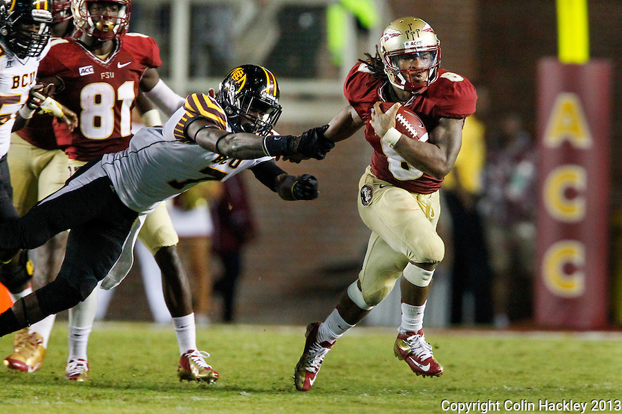 TALLAHASSEE, FLA 9/21/13-FSU-BCC092113CH-Florida State's Devonta Freeman runs as Bethune Cookman's Nick Addison tries to hang onto his arm during second half action Saturday at Doak Campbell Stadium in Tallahassee. The Seminoles beat the Wildcats 54-6.<br /> COLIN HACKLEY PHOTO