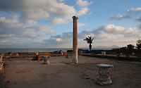 Low angle view of the Gymnasium with columns and capitals in the Antonine Baths, with the sea in the background, Carthage, Tunisia, pictured on January 28, 2008, in the evening. Carthage was founded in 814 BC by the Phoenicians who fought three Punic Wars against the Romans over this immensely important Mediterranean harbour. The Romans finally conquered the city in 146 BC. Subsequently it was conquered by the Vandals and the Byzantine Empire. Today it is a UNESCO World Heritage. Founded in the 2nd Century by the Emperor Hadrian and completed by Antoninus Pius, the Antonine Baths were the largest outside the ancient city of Rome. Today, the basement, furnaces and fragments of carved and inscribed masonry remain of the highly complex structure, which included the Caldaria and Frigidarium (hot and cold baths). Picture by Manuel Cohen.