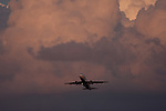 A plane takes off into a dramatic sunlit cloudy sky
