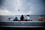 Local Mumbaikars relax and spend time on the sea front of marine drive in Mumbai, India.