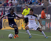 New England Revolution midfielder Sainey Nyassi (17) attempts to control the ball as Philadelphia Union defender Gabriel Farfan (15) defends. In a Major League Soccer (MLS) match, the Philadelphia Union defeated the New England Revolution, 3-0, at Gillette Stadium on July 17, 2011.