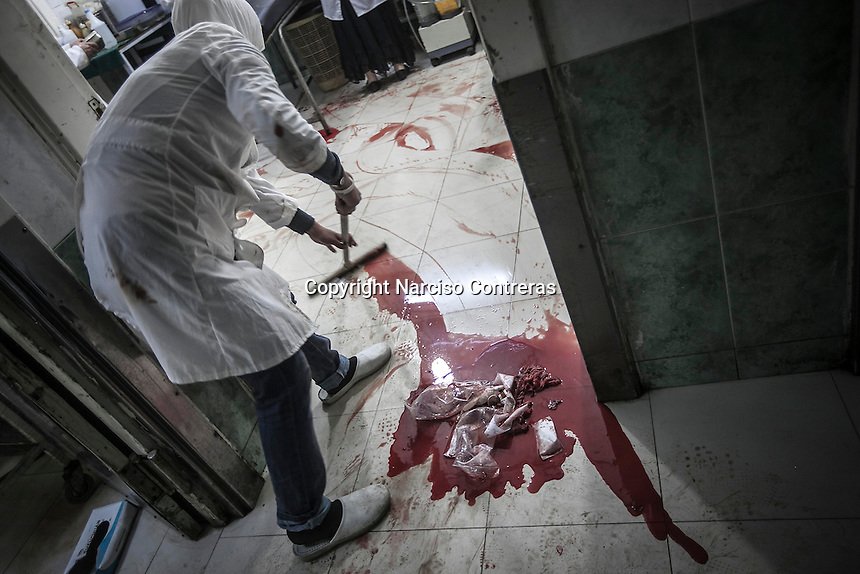 A Syrian volunteer woman cleans up the puddles of blood from the floor of the emergency ward at one hospital after several wounded and dead bodies have arrieved during the haevy shelling in different districts in Aleppo City.
