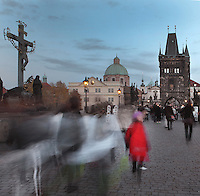 People crossing the Charles Bridge or Karluv most, built 1357 - 15th century, looking towards the Old Town bridge tower, with the Crucifix and Calvary sculpture on the left, across the Vltava river in Prague, Czech Republic. Its construction began under King Charles IV, replacing the old Judith Bridge built 1158'??1172 after flood damage in 1342. This new bridge was originally called the Stone Bridge (Kamenny most) or the Prague Bridge (Prazsky most) but has been the Charles Bridge since 1870. The bridge is 621m long and nearly 10m wide, resting on 16 arches shielded by ice guards. It is protected by three bridge towers, two on the Lesser Quarter side and one in Gothic style on the Old Town side. The historic centre of Prague was declared a UNESCO World Heritage Site in 1992. Picture by Manuel Cohen