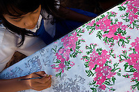A student at Kartini Emergency School paints cloth during a dress making class. Acquiring practical skills is an important part of the education programme. Since the early 1990s, twin sisters Sri Rosyati (known as Rossy) and Sri Irianingsih (known as Rian) have used their family inheritance to set up and run 64 schools in different parts of Indonesia, providing primary education combined with practical skills to some of the country's most deprived children.