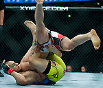 Cub Swanson, yellow trunks, upends Ricardo Lamas during Saturday's UFC on Fox event at the Honda Center.