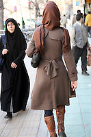 A woman in Western-style clothing passes another woman in a chador on a city street.