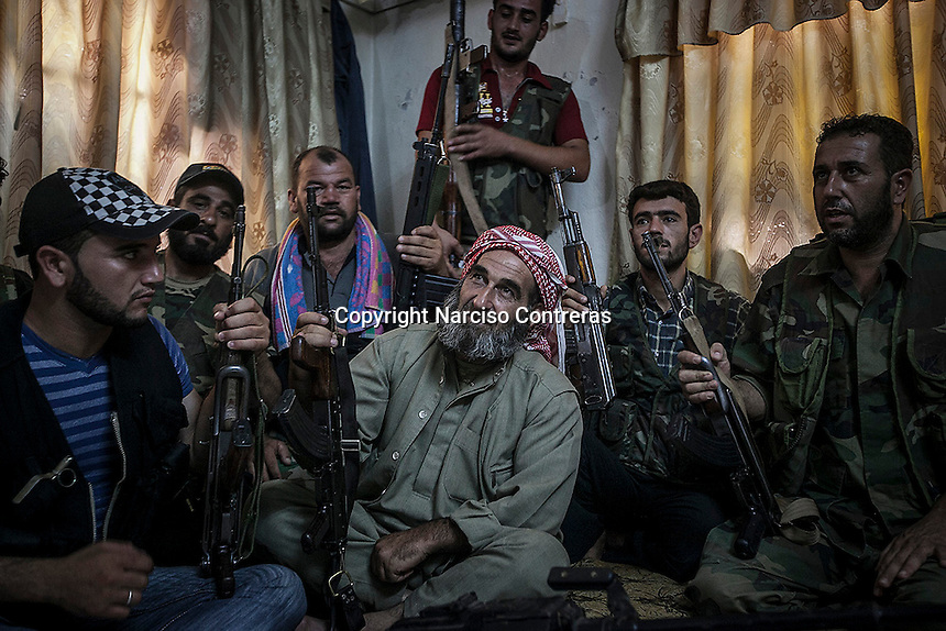 """SHEIK SALAM, leader of a rebel faction of the FSA in Ibeen town, takes a rest with a unit of his men inside a security house, after patroling the city which belongs to the so called """"liberated territory"""" under control of the rebels."""
