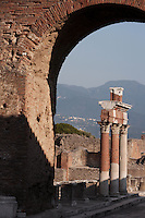Colonnade around the Forum, Pompeii, 2nd century BC. Lit by the strong afternoon sun a group of Corinthian columns, against the misty mountainous background, is framed by an archway.
