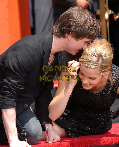"""DANIEL RADCLIFFE & EMMA WATSON.at The Warner Brothers Presents """"Harry Potter and The Order of The Phoenix"""" Hand, Foot & Wand Ceremony held at The Grauman's Chinese Theatre in Hollywood, California, USA, July 09 2007.                                                                                           half length kneeling down hands writing wand talking in ear.CAP/DVS.©Debbie VanStory/Capital Pictures"""