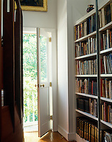 The door at one end of this library leads to the balcony that offers a view of the garden beyond