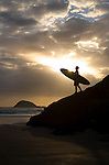 A male surfer is silhouetted at sunset at Muriwai Beach on the west coast of the North Island, near West Auckland, in New Zealand.