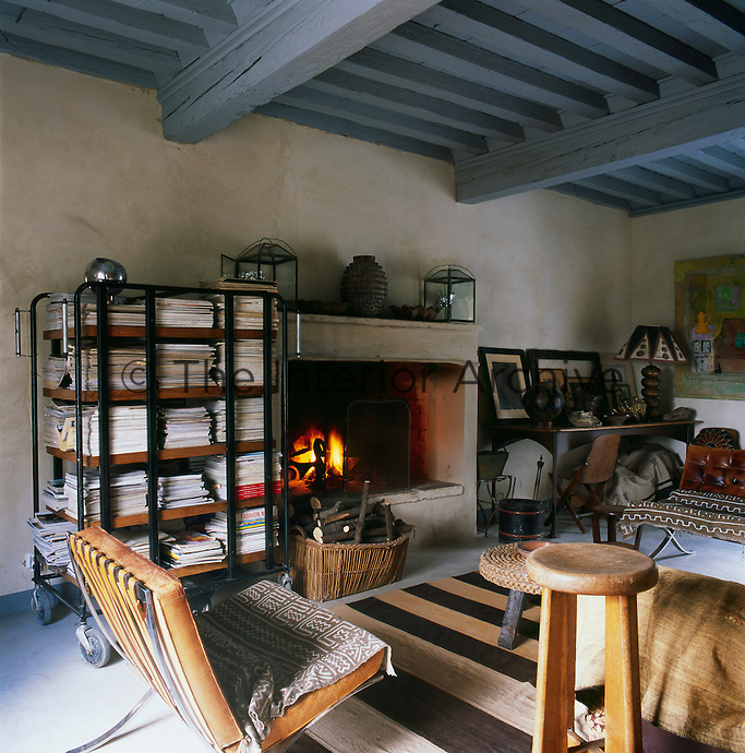 An informal, cosy library with a grey painted beamed ceiling and an open fire in a stone fireplace. A Mies van der Rohe Barcelona chair stands near postal sorting carts, which hold a collection of magazines.