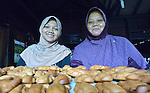 Zaitun (right) and her daughter Nizria show pastries they baked in their home in Banda Aceh, on Indonesia's Sumatra Island. The family lost their house and belongings in the 2004 tsunami. The government provided them with a new house. Church World Service, a member of the ACT Alliance, loaned the women in the neighborhood the money they needed to purchase new equipment and ingredients to restart their businesses. The women repaid their loans to a revolving fund that they jointly manage. Zaitun has used the profits from her pastry business to keep her four children in school. Nizria recently graduated from a local university with a degree in economics, but while she's looking for employment she assists her mother with the pastry making.