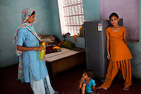 Nafeesa, 27, tends to her children in her house in a slum in Tonk, Rajasthan, India, on 19th June 2012. Nafeesa's health deteriorated from bad birth spacing and over-working. While her husband works far from home, she rolls bidis (indian cigarettes) to make an income and support the family. She single-handedly runs the household and this has taken a toll on her health and financial insufficiencies has affected her four children's healths. Photo by Suzanne Lee for Save The Children UK