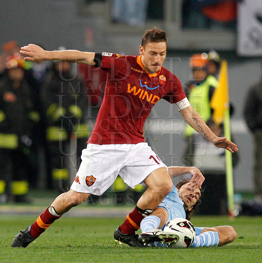 Calcio, Serie A: Roma vs Lazio. Roma, Stadio Olimpico, 8 aprile 2013..AS Roma forward Francesco Totti is tackled by Lazio defender Giuseppe Biava, bottom, during the Italian serie A football match between A.S. Roma  and Lazio at Rome's Olympic stadium, 8 april 2013..UPDATE IMAGES PRESS/Riccardo De Luca