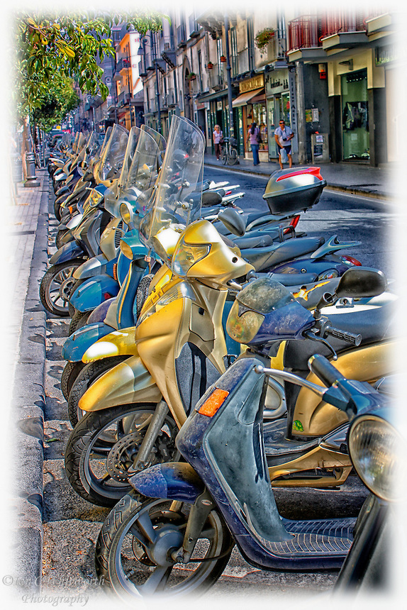 Looking along a line of parked scooters on an Italian street.
