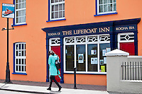 Young woman strolls past The Lifeboat Inn traditional bar in Courtmacsherry, West Cork, Ireland