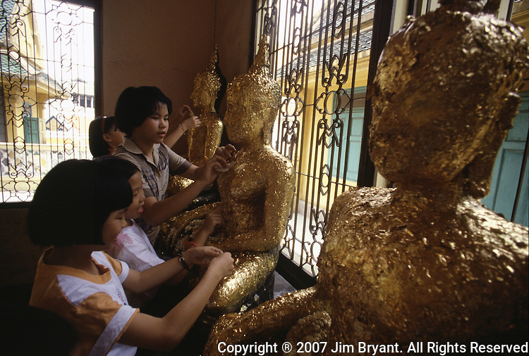 Children rub gold leaf onto images of Buddha in Bangkok, Thailand. (Jim Bryant Photo).....