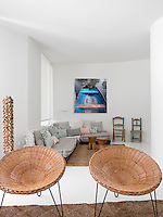 Two distinct seating areas are grouped around straw rugs in the large living room. View over a pair of rattan 'armchairs' from one area to the other