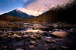 A rocky river overlooking a mountain at sunset.
