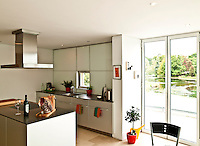 The contemporary kitchen looks onto the river Beaulieu in Hampshire