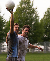 Two muddy soccer teammates walking triumphantly off the soccer field holding the ball above their heads