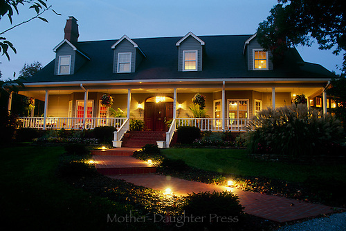 Cape cod style house lit for evening guest arriving for party by well lit walkways and welcoming views, Missouri