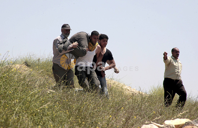 Palestinian villagers from Oref village help a wounded man during clashes with Jewish settlers after Israeli settlers attacked villages near Nablus City 30 April 2013. Reports state that the clashes occured after an Israeli settler was stabbed to death by a Palestinian man. Israeli media reported that the Palestinian attacker took the settlers' weapon and began firing at a nearby Israeli border guard force, who returned fire, wounding the attacker. Photo by Nedal Eshtayah