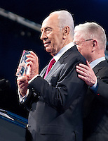 President of Israel Shimon Peres shows off an award he received following his speech at the American Israel Public Affairs Committee (AIPAC) Policy Conference in Washington, D.C. on Sunday, March 4, 2012 prior to United States President Barack Obama delivering his remarks. .Credit: Ron Sachs / Pool via CNP /MediaPunch