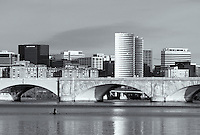 A lone morning rower travels up the Potomac River from the Arlington Memorial bridge, with buildings of Arlington, VA in the background